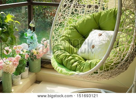 garden swing with mattress and cushion in a balcony in the morning