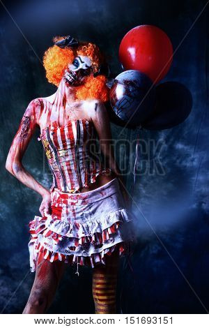 Evil redhead clown stained in blood holding balloons. Female zombie clown. Halloween. Horror.