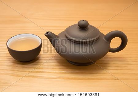 side view cup of tea and teapot on wood table