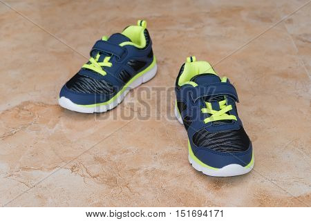 pair of blue stylish shoes for kid on floor