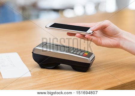 Woman paying with nfc technology on smart phone. Woman paying bills on mobile phone with card swiping machine. Close up of customer hand making payment by smartphone with NFC.