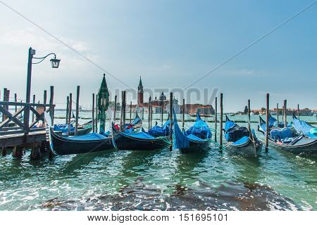 Several black gondolas, covered with a blue overlays, are hitched to the wharf next to the San Marco Basilica in Venice, Italy. In the background a San Giorgio Island can be seen.