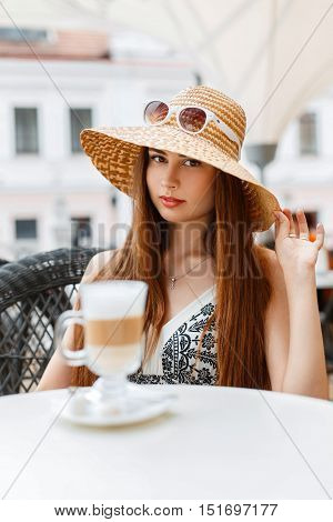 Beautiful Woman In A Straw Hat And Sunglasses Resting In A Summer Cafe And Drink Coffee.
