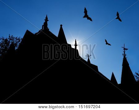 halloween background with silhouettes of castle roofs with weathervanes and three flying bats