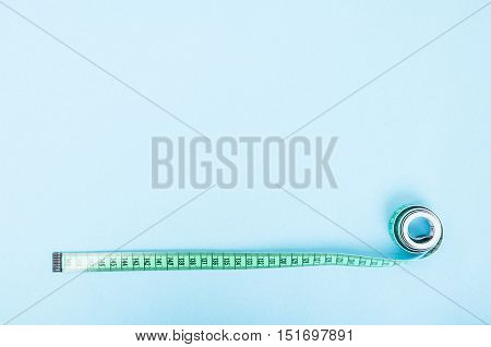 Green Measure Tape Rolled On Blue Background