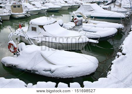 Cecina Marina Livorno Tuscany - snowfall in the seaside town the harbor with boats at the pier