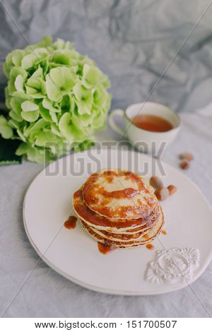 white cup and plate with pancakes green hydrangea