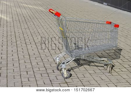 Shopping supermarket cart stands on the pavement .