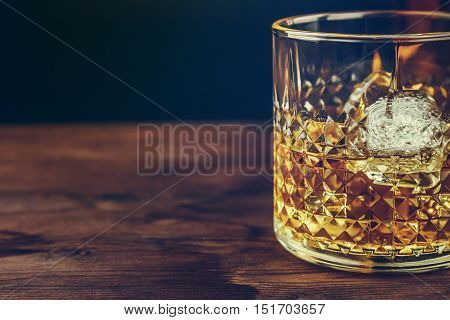 Glass Of Whiskey With Ice Cubes On Wood Table, Warm Atmosphere