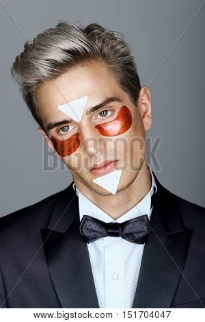 Elegant man with red eye patches. Portrait of dramatic man with perfect skin. Grooming himself.
