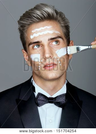 Fashion man with cosmetic cream treatment on his face. Portrait of very handsome man in elegant suit. Skin care concept