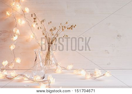 Burning lights and decoration on white wooden background. Interior.