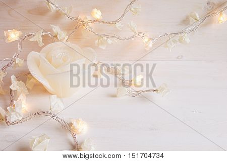 Burning lights and candle rose on white wooden background. Christmas background.