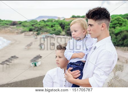 Three brothers admire the sea, thoughtfully looks afar