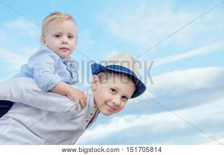 Portrait of a smiling boy giving his brother a piggyback ride outdoors against the sky.