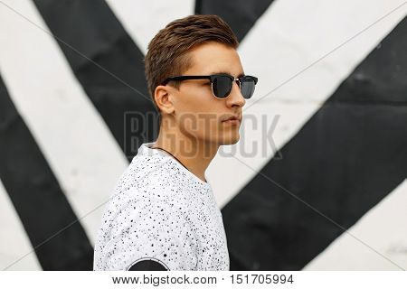 Young Handsome Guy With A Hairstyle And Sunglasses On A Background Of Black And White Stripes.