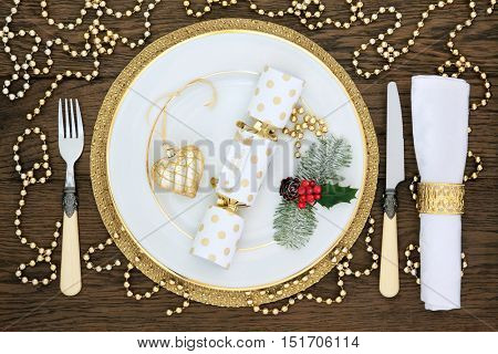 Christmas dinner table setting with white porcelain plate, cracker and gold bead decorations, holly, cutlery and napkin over oak wood background.