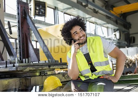 Young manual worker talking on mobile phone in metal industry