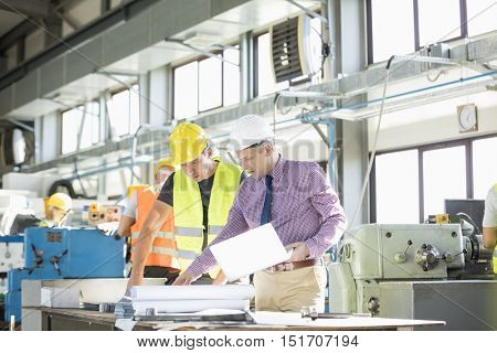 Architect and manual worker examining blueprint at table in industry