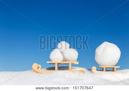 Two Sledges With A Lots Of Snowballs In Front Of A Blue Sky