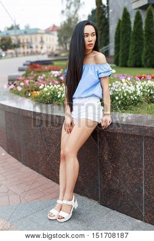 Asian Pretty Woman In A Fashionable Blouse With Bare Shoulders And White Shorts Is Posing Against Th
