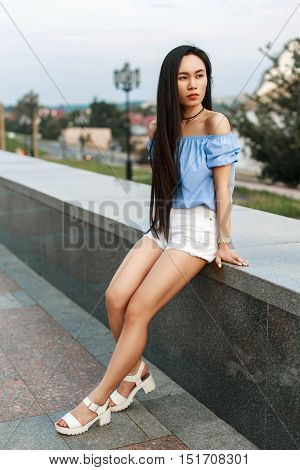 Beautiful Young Girl In Stylish Blue Blouse And White Shorts On A Background Of The City