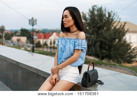 Beautiful Fashionable Asian Woman In A Blue Blouse And White Shorts With A Bag Sits On A Background