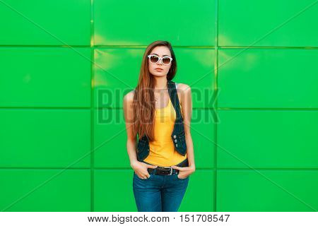 Young Fashionable Woman In A Yellow T-shirt And Denim Vest Posing Near The Green Wall.