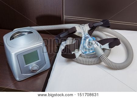 CPAP machine with air hose and head gear mask in a bedroom