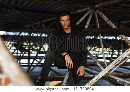 Stylish Young Man In A Hood In Black Robes Is Posing On A Background Of Metal Pipes
