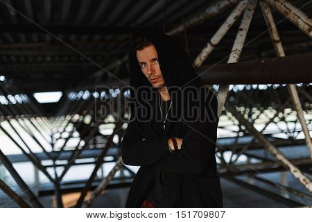 Handsome Fashionable Man In A Stylish Robes With A Hood Near Metal Structures
