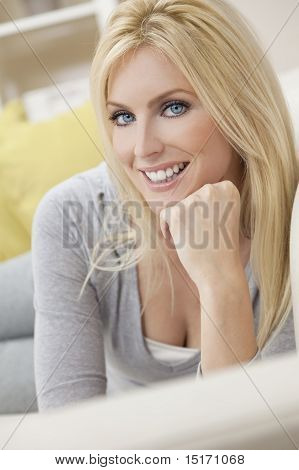 Happy Blond Woman With Blue Eyes Resting On Her Hand