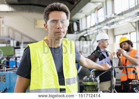 Portrait of mid adult worker wearing protective eyewear with colleagues in background at industry