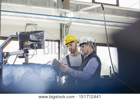 Male manual workers operating machinery at metal industry