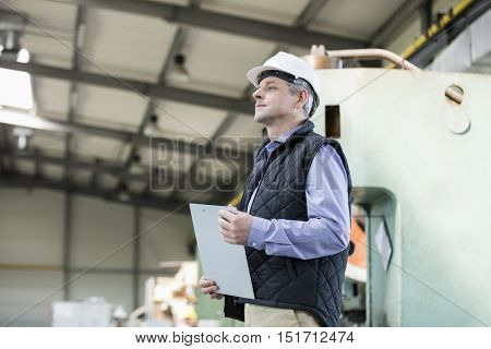 Side view of male supervisor holding clipboard in metal industry