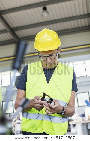 Mid adult manual worker measuring metal with caliper in industry