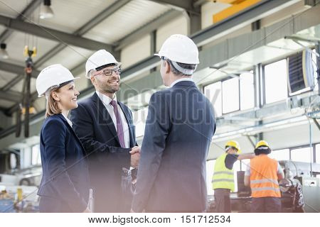 Businessmen shaking hands with workers working in background at metal industry