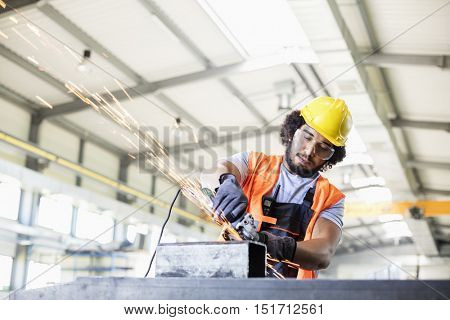 Young manual worker using grinder on metal in factory