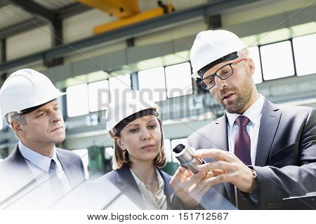 Mid adult businessman explaining machine part of colleagues in metal industry