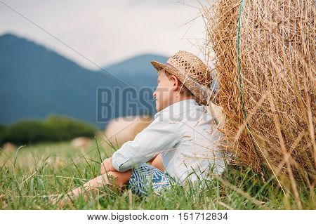 Rural photo: a boy sits near the stack of hay in the meadow