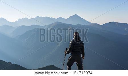 Hiker With Trekking Poles Admires Ridge In The Morning.