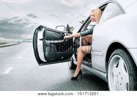 Young beautiful fashionable woman gets out of a car