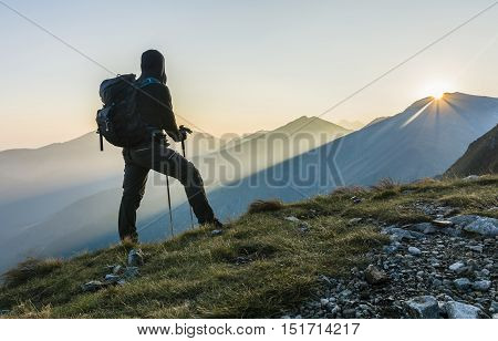 Hiker With Trekking Poles And Backpack.