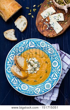 Creamy butternut squash soup with blue cheese, thyme, pumpkeen seeds and bread