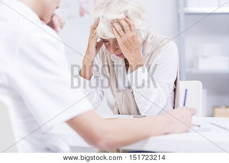 Elder Woman Sitting In A Doctor's Office