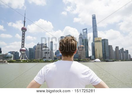 Rear view of man looking at Pudong skyline against cloudy sky