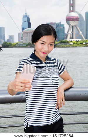 Smiling woman taking selfie through smart phone while standing against Oriental Pearl Tower