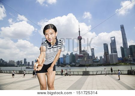 Portrait of happy woman gesturing peace sign while standing on promenade against Pudong skyline