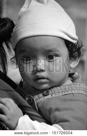 CHICHICASTENANGO GUATEMALA APRIL 29 2016: Portrait of a Mayan baby carried on the back of his mother. The Mayan people still make up a majority of the population in Guatemala,
