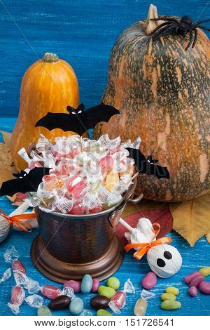 Halloween composition with pumpkins candy bucket paper bats rubber spider dry leaves and candies on blue wooden backround